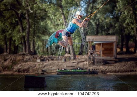 Woman in a jump with a board she is an extreme sportsman in training.
