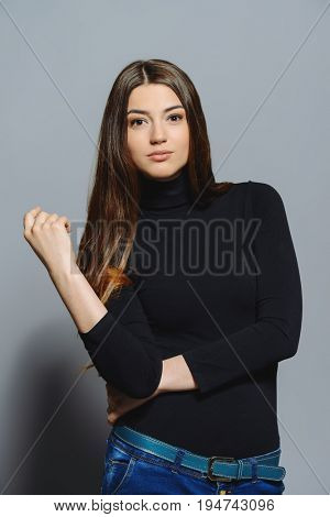 Portrait of calm and confident young woman with long brown hair and beautiful eyes. Hairstyle, healthy hair. Cosmetics and make-up.