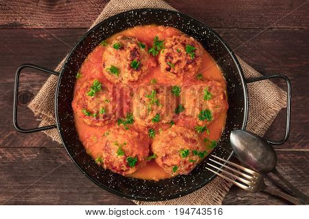 An overhead photo of meatballs in tomato sauce, shot from above in the skillet on dark rustic textures, with a fork and a spoon, and a place for text