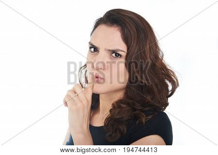 Woman show silence sign isolated on white background. Young woman hold finger next to lips