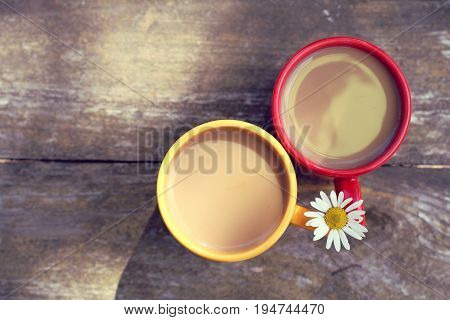 Coffee with cream in a red and yellow mug decorated with chamomile top view / summer coffee break