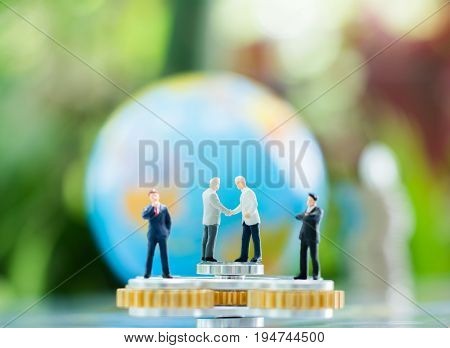 Miniature businessman handshaking on the fidget spinner with blurred globe and stack of coins using as background commitment agreement investment and partnership concept.