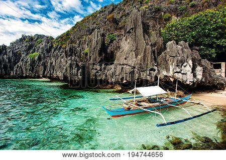 El Nido Palawan Philippines. Philippine boat in turquoise clean water with sharp rocks a background. Tropical country. wide angle
