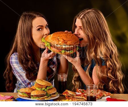 Women eating fast food. Gils eat hamburger with ham. Two female bite burder junk from two sides on dark background . People try to feed each other. Girl friends are dining in cafe.