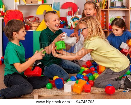 Children building blocks in kindergarten. Group boys and girls playing toy on floor . Interior preschool. Little ones develop their fingers in game of cubes. Development of social skills in kids.