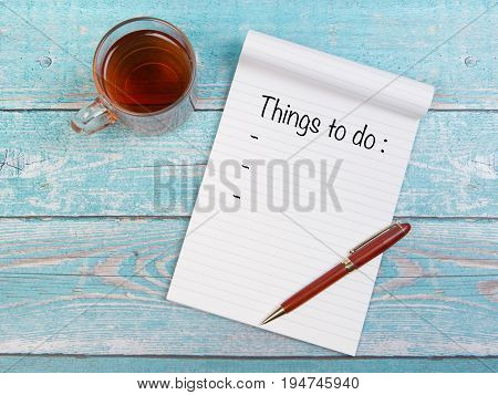 Notebook with things to do text written on it with a cup of tea and a pen on a blue wooden table seen from above
