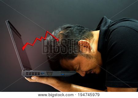Asian man 40s holding computer laptop with stress in stock market graph business fall down concept