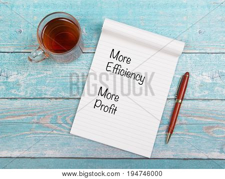 Notebook with business goal of more efficiency and more profit with a cup of tea and a pen on a blue wooden table seen from above