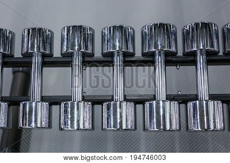 Rows of metal dumbbells on rack in the gym or sport club. Weight Training Equipment