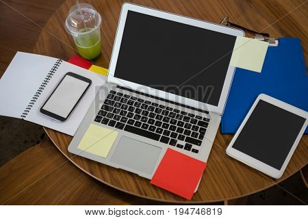 High angle view of laptop with mobile phone and digital tablet on wooden table in office
