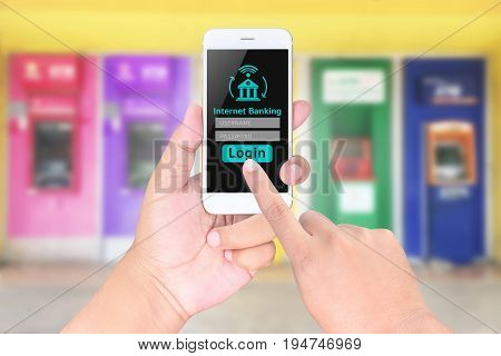 Man Hands Hold Mobile Banking On A Smart Phone On Blurred Abstract Background Of Atms Machine