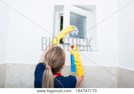 Young Woman Wiping Small Window At Home