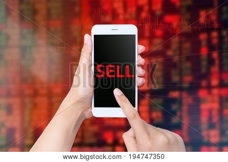 Hand Holds Smart Phone Showing Sell Over The Stock Market Chart Background