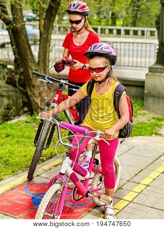 Family bike ride. Mother and daughter wearing bicycle helmet with rucksack. Children biking on yellow bike lane. Bike share program save money and time. Child sisters learn to ride bicycle.