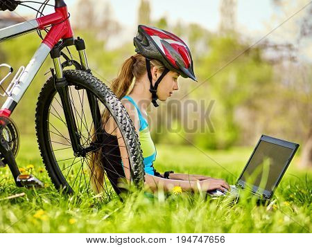 Woman traveling bicycle in summer park. Bicyclist girl watch on laptop. Girl counts pulse after sport training and is looking for way to navigator. Dependence on social networks. Person makes money on