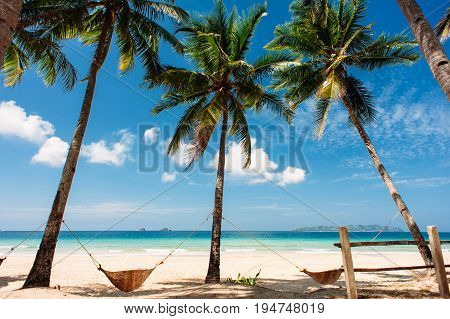 tropical beach with white sand and palm trees with two hammocks blue sky with clouds clear sea. Nacpan beach Palawan Philippines. Wide angle.