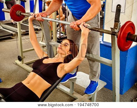 Fitness friends workout gym. Woman working on bench press. She lifting barbell. Trainer backs girl while taking exercises. Girl breathes deeply and heavily.