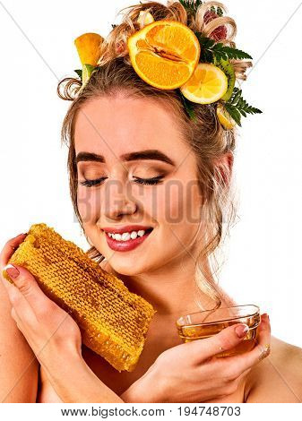Honey facial mask with fresh fruits for hair and skin on woman head. Girl with beautiful face hold honeycombs for homemade organic skin and hair therapy. Healing properties of natural honey.