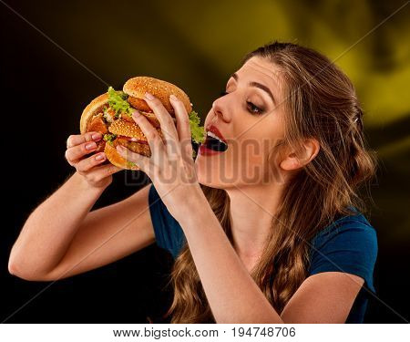 Woman eating hamburger. Student consume fast food on table. Cook teaches to cook and shares recipes. Girl eagerly eats junk alone without embarrassment. Delivery of food at home.