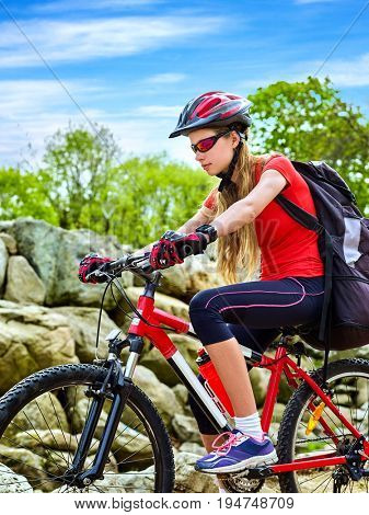 Woman on bicycle ride mountain. Girl traveling in summer park. Early morning with blue sky and clouds. Cycling person with rucksack. Female loves extreme sports.