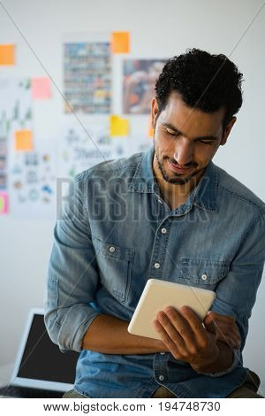 Young man using digital tablet against adhesive notes at creative office