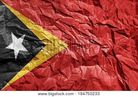 East Timor flag painted on crumpled paper background