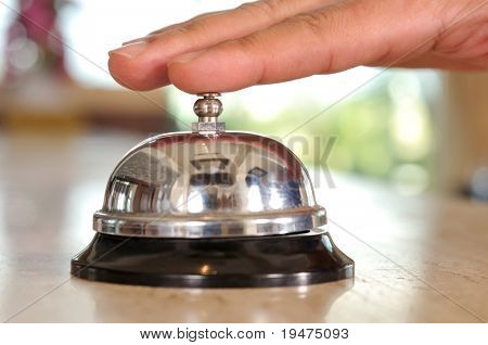 Hand of a man using a hotel bell - a series of HOTEL images. poster