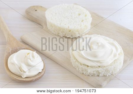Sour cream on slice of round bread and a wooden spoon with sour cream on kitchen table.
