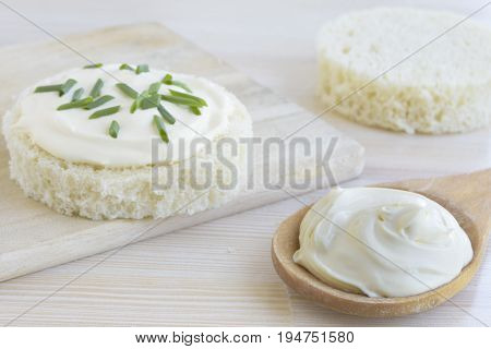 Sour cream in wooden spoon  and a slice of round bread with sour cream and spring onions on wooden table.