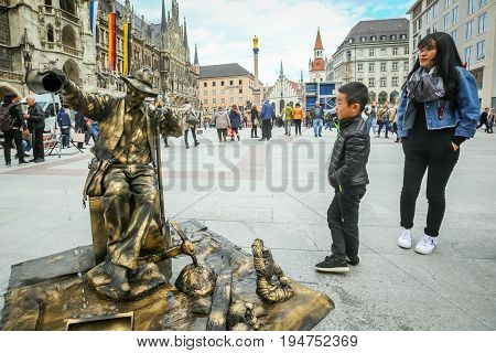 MUNICH GERMANY - MAY 9 2017 : A boy and mother watching a street entertainer disguised as a sculpture fountain with people in the background sightseeing Marienplatz in Munich Germany.