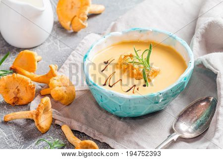 Mushroom cream soup with chanterelles, balsamic and herbs on gray rustic background