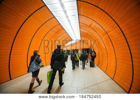 MUNCHEN GERMANY - MAY 9 2017 : People in transit on the Marienplatz subway station walking through a tunnel passage in Munich Germany. About 350 million passengers ride the U-Bahn every year.