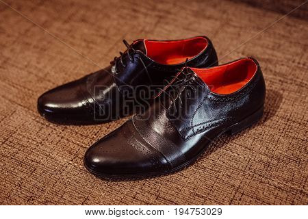 Stylish Black Leather Shoes Stand On The Brown Carpet
