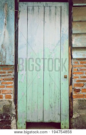 The old blue wood door is decaying , close up
