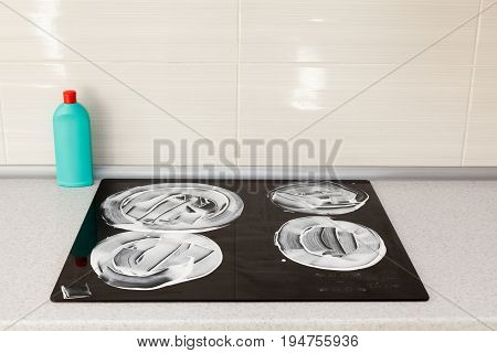 The surface of the induction stove is covered with a detergent. House cleaning - plastic bottles with detergents on kitchen tabletop on the background of electric stoves.