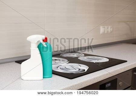 House cleaning - plastic bottles with detergents on kitchen tabletop on the background of electric stoves. Cleaning of induction stove.