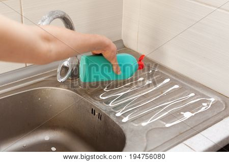 Woman hands with bottle of cleaning detergent for metal sink in the kitchen