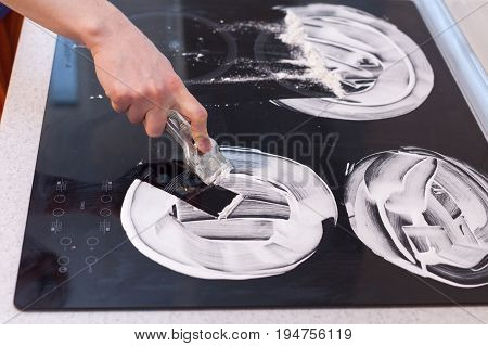 House cleaning. Housewife cleaning and polish electric cooker. Black shiny surface of kitchen top hands with foam glass scraper bottle of cleaning agent