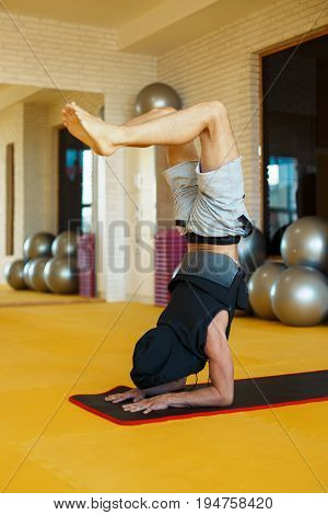 Handsome Young Man In Hood Working Out, Yoga, Pilates, Fitness Training, Doing Handstand, Scorpion P