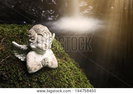 praying stone angel on moss in front of waterfall with sunbeam