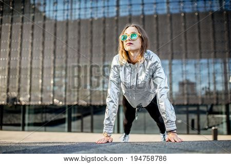 Lifestyle portrait of a stylish woman in silver jacket exersicing outdoors in the modern urban environment