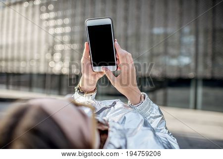 Womn using smart phone with empty screen to copy paste lying outdoors in the modern environment