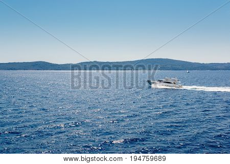A Small Speedboat Sails Along The Calm Waters
