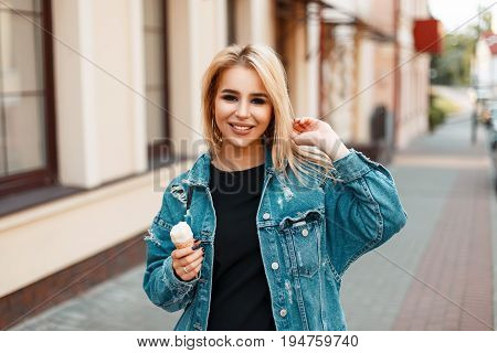 Beautiful Happy Young Woman With A Smile And A Good Mood With Ice Cream In Jeans Clothes Walking In