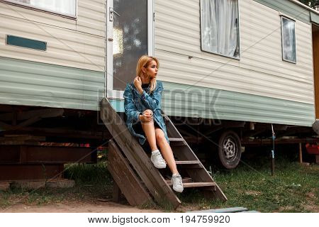 Beautiful American Woman In Stylish Jeanswear With Shoes Sitting Near A Metal Vintage Trailer