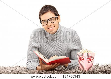 Nerdy guy with a book and popcorn looking at the camera and smiling isolated on white background