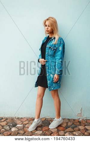 Beautiful Stylish Blond Girl In A Denim Jacket With Sneakers Near A Blue Wall On A Summer Day
