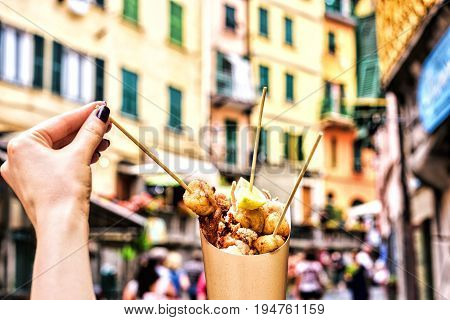 Seafood in Cinque terre Italy liguria. holding fresh delicious fried fish specialities at street background