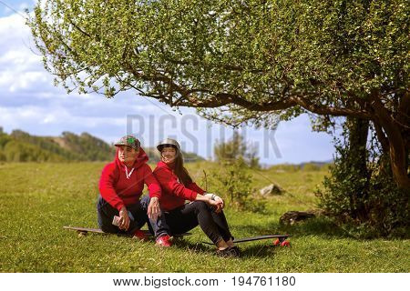 A young man and his girl with longboards are resting near a tree on a sunny day.