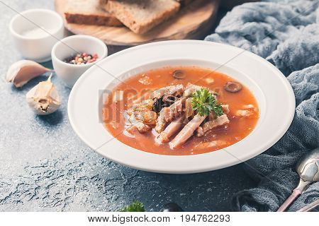 Soup with meat, olives, herbs, lemon in white bowl, black bread and spices on gray background, homemade food. Traditional Russian soup - solyanka